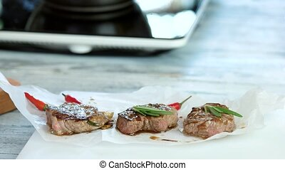 Meat medallions with herb. Rosemary and small chili peppers.