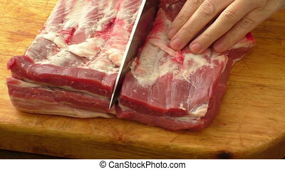 Meat on board and hands. Knife cutting raw pork