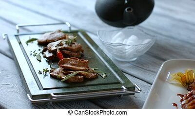 Meat on dark green tray. Kettle pours liquid into bowl. Dry...