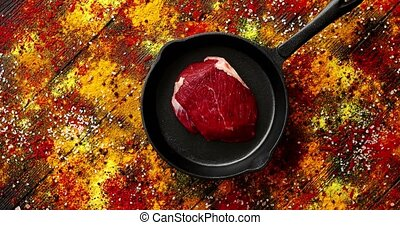 Meat on pan laid on surface with spilt spices - From above...