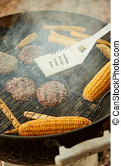 Meat patties and corn on the cob on a barbecue