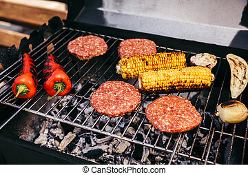 Meat patties and vegetables cooked outdoors on grill