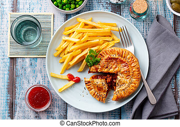Meat pie with french fries on a plate. Wooden background. Top view.