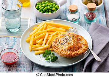 Meat pie with french fries on a white plate. Wooden background. Close up.