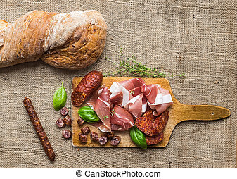 Meat selection / wine set on a rustic wood board over a rough sackcloth background