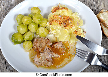 meat platter with gratin potatoes and Brussel sprouts