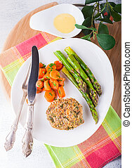 Meat rissole with glazed carrots, asparagus on the plate.
