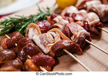 Meat rolls with bacon on stick