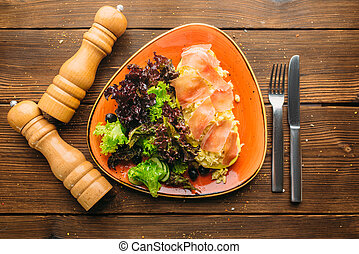 Meat salad in a bowl on wooden table, top view