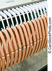 Meat sausages on plastic conveyer in food industry - Meat...