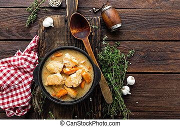 Meat stewed with carrots in sauce and spices in cast iron pan on dark wooden rustic background top view flat lay