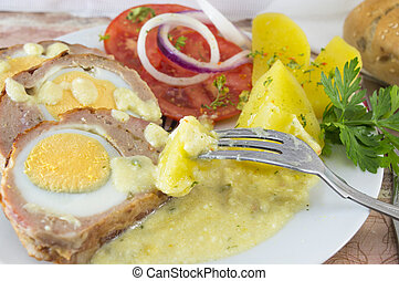 Meat with potatoes and tomatoes on a plate