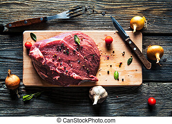 Meat with spices and vegetables on wooden background. Knife. food