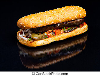 Meat with vegetables in a bun on a black background.
