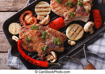 meat with vegetables in a pan grill closeup. Top view horizontal