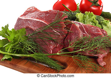 Meat with vegetables on cutting board