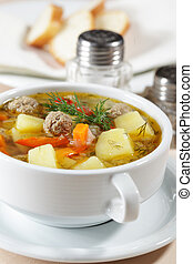 Meatball soup with vegetables closeup