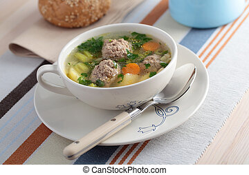 Meatball soup with vegetables on a table
