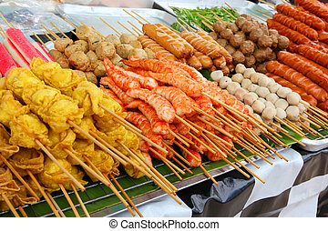 Meatballs and fried shrimps on sticks at a market in Phuket...