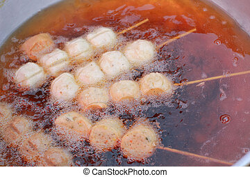Meatballs frying in a pan