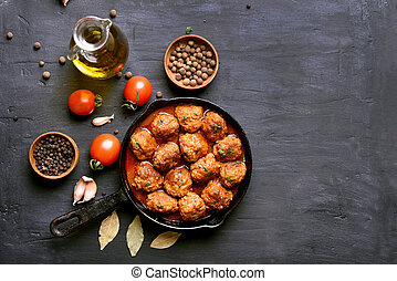 Meatballs in frying pan on dark background with copy space, top view