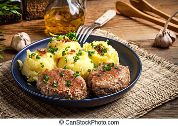 Meatballs served with boiled potatoes.