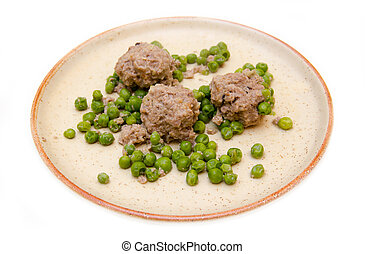 Meatballs with peas on plate on white background