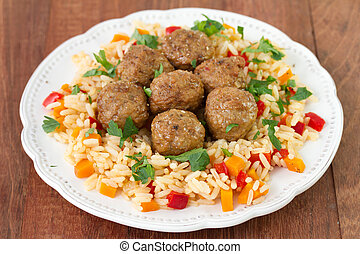 meatballs with rice with vegetables on white plate