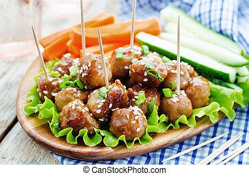 meatballs with Teriyaki sauce and sesame seeds on a white...