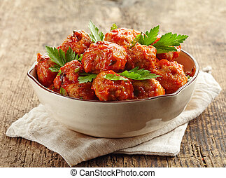 Meatballs with tomato sauce in a bowl on wooden table