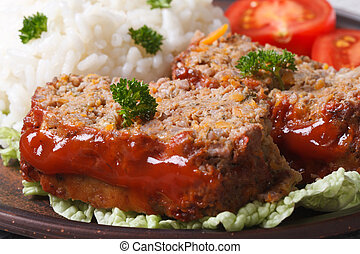 meatloaf with rice and vegetables on a plate macro