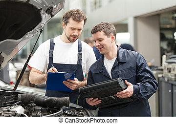 mecánica, en el trabajo, shop., dos, confiado, mecánica, discutir, algo, mientras, uno, de, ellos, teniendo tablilla sujetapapeles