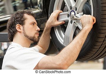 mecánico, en, work., confiado, mecánico, trabajo encendido, un, rueda de coche, en, el, taller de reparaciones