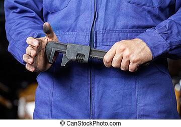 mecánico, sostener la llave, en, taller de reparaciones