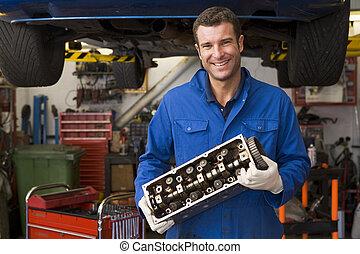 mecânico, segurando, parte carro, sorrindo
