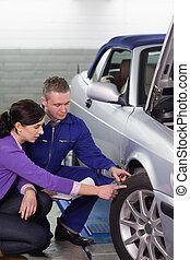 mecânico, tocar, a, roda carro, perto, um, mulher