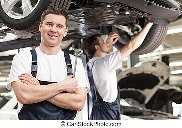 mecanica, no trabalho, shop., confiante, jovem, mecânico, ficar, com, seu, braços cruzaram, e, sorrindo, câmera, enquanto, outro, um, trabalhar, a, fundo