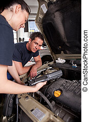 Mechanic - A team of mechanics using an electronic...