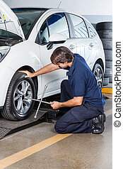 Mechanic Adjusting Car Tire With Rim Wrench At Garage