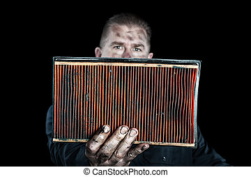 Mechanic and air filter - An auto mechanic holds up a...