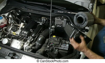 Mechanic Assembles Air Filter - A repairman mounting the air...