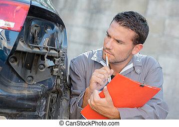 Mechanic assessing a car