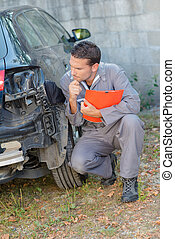 Mechanic assessing damage to rear of car