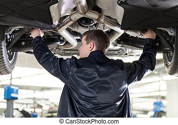 Mechanic at work. Confident auto mechanic working at the repair shop while standing under the car