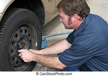 Mechanic at Work - A mechanic removing lug nuts from a tire....