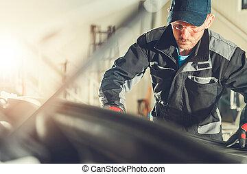 Mechanic At Workshop Checking Under Hood Of Car.