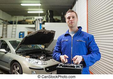 Mechanic carrying car battery - Portrait of male mechanic...