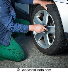 mechanic changing a wheel of a modern car