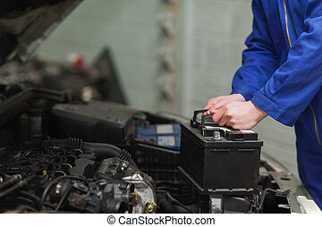 Mechanic changing car battery - Male mechanic changing car...