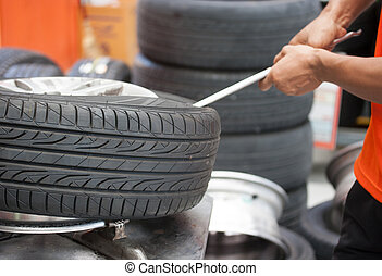 Mechanic changing car tire closeup - Close-up of Mechanic...